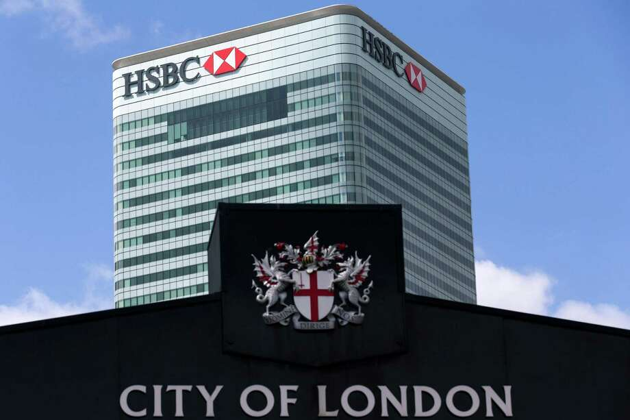 (FILES) In this file photo taken on June 09, 2015 HSBC's headquarters stands beyond Billingsgate Fish Market in east London on June 9, 2015. Scandal-hit bank HSBC said today it would cut its global headcount by up to 50,000 as part of a restructuring that entails its withdrawal from Brazil and Turkey, while it also mulls abandoning London as its HQ.   AFP PHOTO / JUSTIN TALLIS The image of the British financial sector is of a world of overpaid men, a symbol of glaring wage inequalities and women's difficulties in gaining access to the highest positions. New regulations have forced the big names in British finance to publish wage differentials between men and women and the numbers are not flattering. / AFP PHOTO / Justin TALLISJUSTIN TALLIS/AFP/Getty Images Photo: JUSTIN TALLIS, Contributor / AFP/Getty Images / AFP