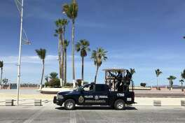 Agents of the Federal Police's gendarmerie patrol on board a SUV in La Paz, Baja California Sur state, Mexico on March 12, 2018.  Despite a surge of violent crimes in popular tourist areas such as Los Cabos and Cancun, tourism is Mexico's third largest source of foreign exchange. In 2017 the country hit a new record of 39.3 million tourists who generated an income of $21 billion. / AFP PHOTO / DANIEL SLIM        (Photo credit should read DANIEL SLIM/AFP/Getty Images)