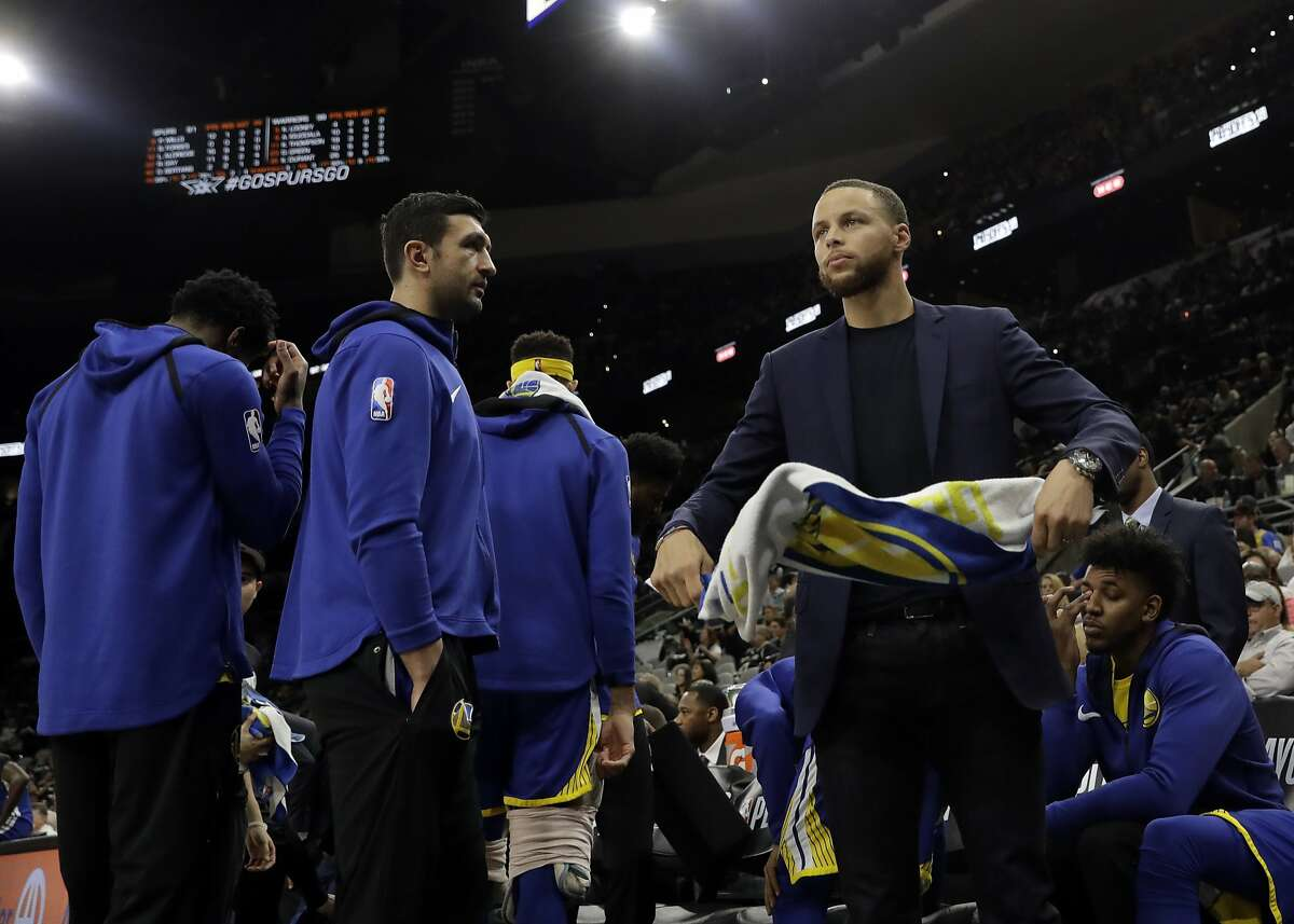 Golden State Warriors' Zaza Pachulia, left, watches as Stephen Curry, right, spins a towel in his hands in the second half of Game 3 of a first-round NBA basketball playoff series against the San Antonio Spurs in San Antonio, Thursday, April 19, 2018. Golden State won 110-97.