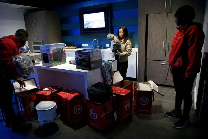 From left: Omni's operations manager Anthony Monroe delivers to client Tiffany Zhong as she prepares for her party, Wednesday, April 18, 2018, in San Francisco, Calif. Omni offers on-demand storage. People who store stuff there can rent it out to others and Omni delivers and picks it up for them.
