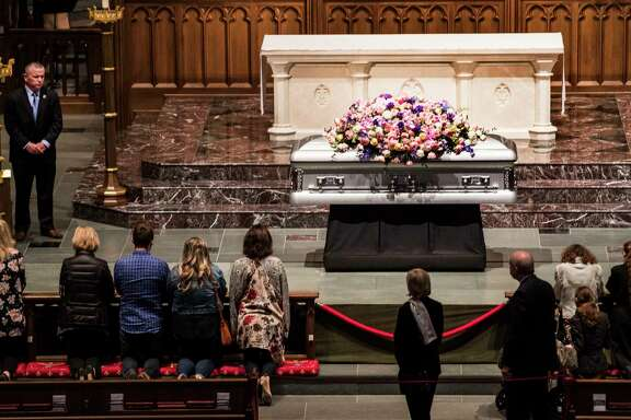 Mourners kneel in prayer in front of former first lady Barbara Bush's casket as she lay in repose inside St. Martin's Episcopal Church on Friday, April 20, 2018, in Houston.