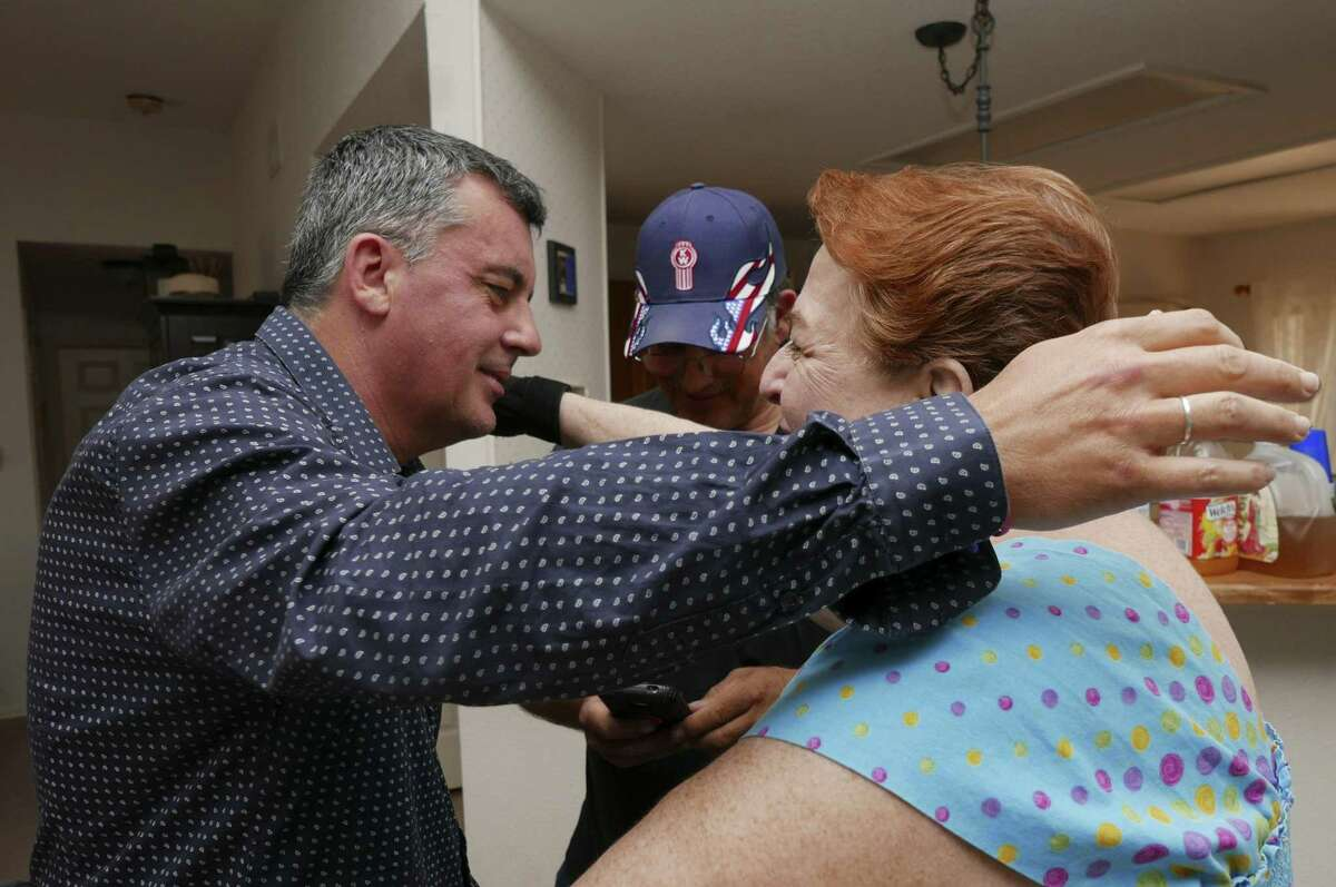 """John Wayne Nelson, who is French and authored a book called """"How I Found My Dad in Texas: DNA Never Lies,"""" greets American family member Karen Nelson during a gathering in San Antonio recently."""
