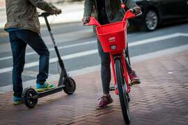 People ride a Uber Technologies Inc. Jump Bike pedal electric bicycle, right, and a Bird Rides Inc. shared electric scooter in San Francisco, California, U.S., on Friday, April 13, 2018. GPS-enabled�scooters�and bicycles are spreading across several major U.S. cities, driven by a wave of venture capital into a handful of companies.�Policymakers are scrambling to find ways to regulate the�great scooter boom of 2018. Photographer: David Paul Morris/Bloomberg