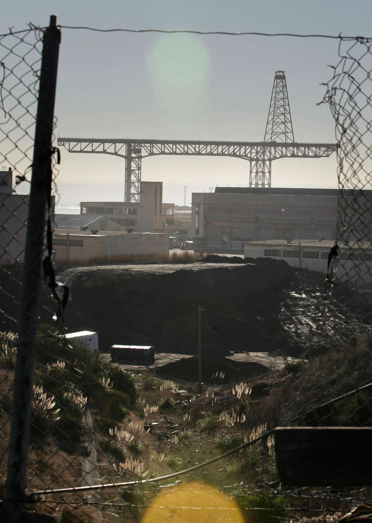The crane and part of the former Hunters Point Naval Shipyard is seen through a hole in a fence on Friday, October 30, 2015 in San Francisco, Calif.