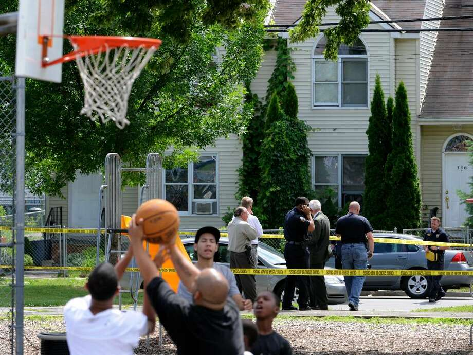 Just beyond the crime scene tape, a basketball game is underway at Jerry Burrell Park in Schenectady where an 11-year-old boy collapsed in the park after he was shot in the head Wednesday. A 20-year-old man was shot nearby and police also dealt with a stabbing during a chaotic afternoon in Schenectady.  (Skip Dickstein/Times Union) Photo: Skip Dickstein / 2008