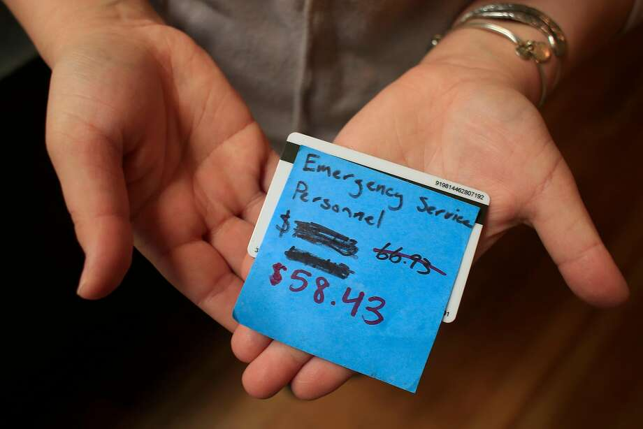 Karly Walzer, co-owner of Blue Beagle Coffee, holds a gift card supplied with funds to be used for emergency responders at the Santa Rosa shop. Photo: Lea Suzuki / The Chronicle