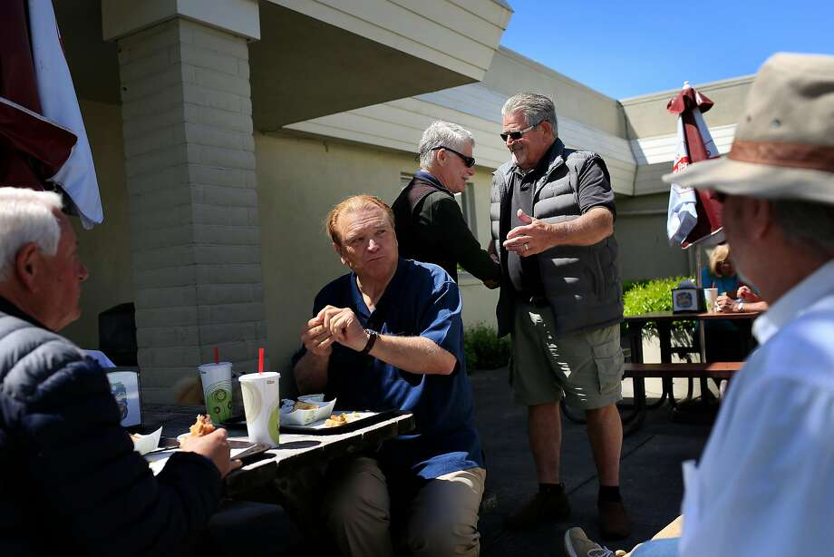 Fiori's Buns and Burgers owner George Fiori (second from right) greets Tom Klinker as he and lifelong friends John Pearson (left), Bill Kuziara and Ron Lester gather for a reunion outside the restaurant Photo: Lea Suzuki / The Chronicle