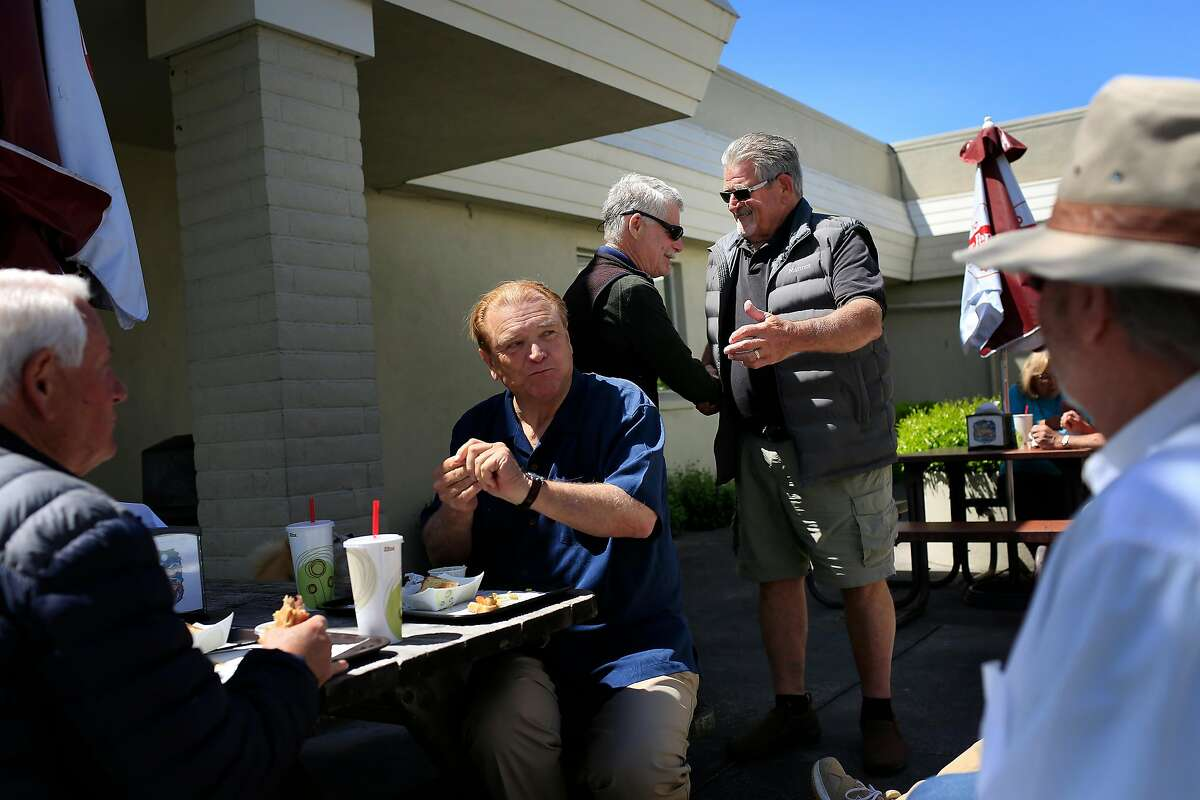 Buns and Burgers owner George Fiori (second from right) greets childhood friend Tom Klinker (center) as he and other childhood friends including John Pearson (left), of Forestville, Bill Kuziara (second from left) of Sebastapol and Ron Lester (right) of Healdsburg gather for a mini reunion during Klinker's visit outside of Buns and Burgers at Larkfield Center on Tuesday, April 17, 2018, in Santa Rosa, Calif.