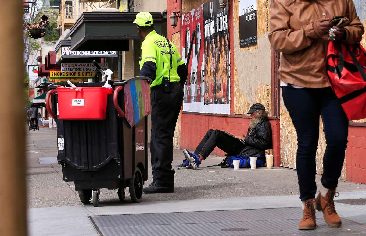 Berkeley ambassador Ernest Watson, (left) cleans the sidewalks as Tu (didn't give his last name) who is homeless says he would miss the paper cups he uses for his coffee and to panhandle with along University Ave. in Berkeley, Calif., as seen on Wed. April 18, 2018. A proposal is underway in Berkeley that would try to eliminate nearly all single-use coffee cups and take-out food containers.