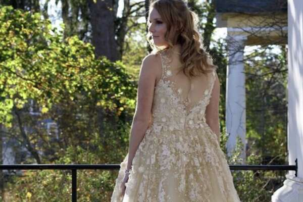 A model shows off a champagne-colored ballgown embellished with floral appliqué. Ballgowns are one of the biggest trends for prom 2018.
