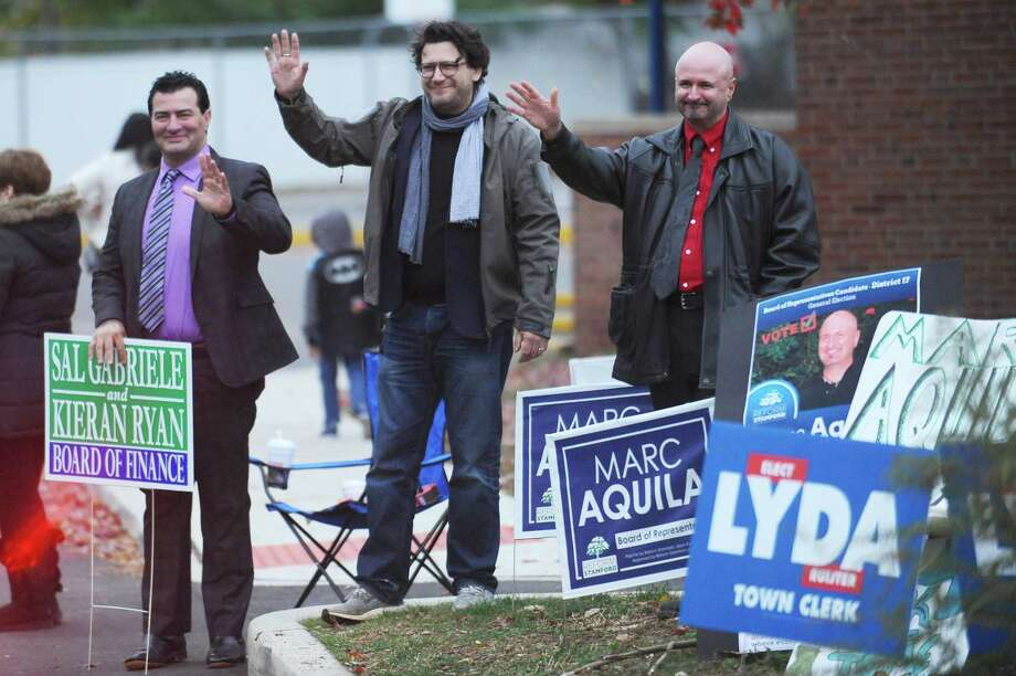 From left, Sal Gabriele, Marc Aquila and David Michel wave to voters as they enter the parking lot of Springdale School in Stamford on Tuesday, Nov. 7, 2017. Photo: Michael Cummo / Hearst Connecticut Media / Stamford Advocate