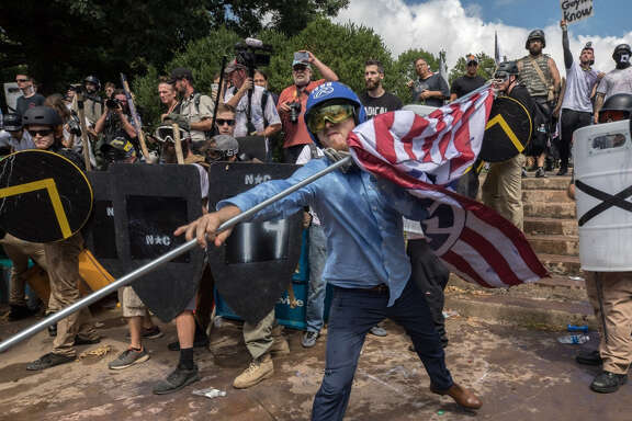 William Fears, center holding the flag, of Houston, is pictured with other white supremacists at a Unite the Right rally in Charlottesville in August. The loose collection of white supremacist groups known as the alt-right movement has suffered significant setbacks since then.