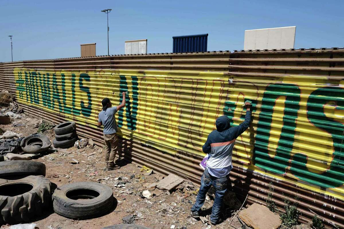 """Activists paint the US-Mexico border wall, as part of the """"Picnic prototype, Security through Friendship"""" activity at the border near President Donald Trump border wall prototypes, in Tijuana, northwestern Mexico on April 14."""