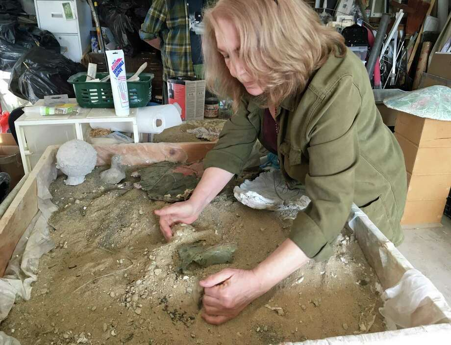 Bethel artist and sculptor Elizabeth White demonstrates how she forms a mold in the sand for her concrete sculptures. Photo: Christina Hennessy / Hearst Connecticut Media / Connecticut Post