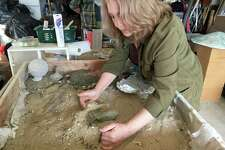 Bethel artist and sculptor Elizabeth White demonstrates how she forms a mold in the sand for her concrete sculptures.
