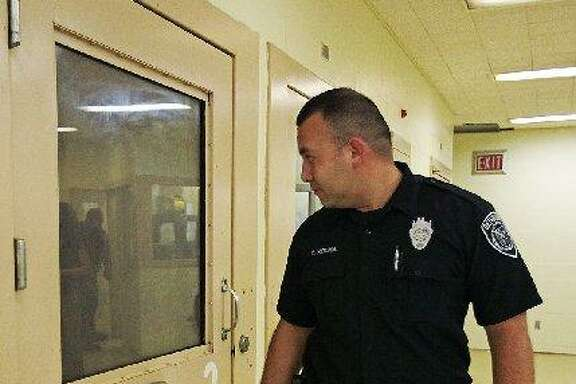 Deputy Cruz Rocha makes the round of the 10 cells of the suicide prevention unit of the Bexar County Jail in 2010. A new state task force will look at betters ways of treating the mentally ill.