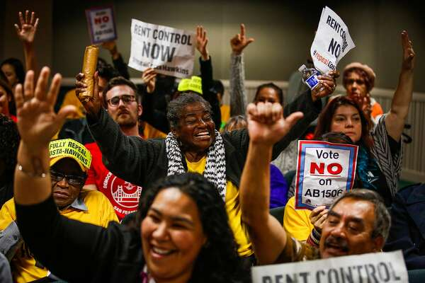 Bonbon Hurd (center), Yesenia Miranda Meza (bottom left), and Jose Diaz (bottom right) put their hands up in excitement during the public comment portion of a hearing on whether or not to repeal the Costa-Hawkins Rental Housing Act at the State Capital in Sacramento, Calif., on Thursday, Jan. 11, 2018.  The Costa-Hawkins Rental Housing Act did not pass.