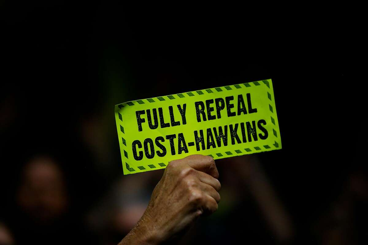 A person holds up a sign in support of a full repeal of the Costa-Hawkins Rental Housing act during the public comment portion of the hearing at the State Capital in Sacramento, Calif., on Thursday, Jan. 11, 2018. The Costa-Hawkins Rental Housing Act did not pass.