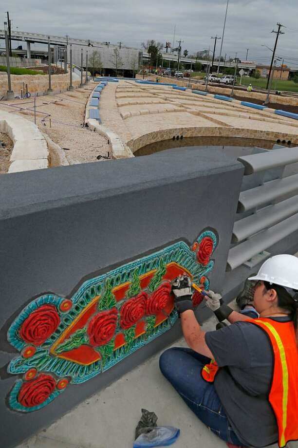 """Alyssa Farmer puts grout on the overpass by the Plaza de Fundacion. Bexar County Judge Nelson Wolff, Commissioner Paul Elizondo and River Authority general manager Suzanne Scott are attending a tour of the San Pedro CreekImprovements Project one month before the first segment of the project opens on May 5 for the Tricentennial celebration week. The segment runs from the flood tunnel inlet at N. Santa Rosa Street near Fox Tech High School to Houston Street. As part of the tour, the creek's """"Culture Park logo"""" will be unveiled Photos taken on Thursday, April 5 ,2018 Photo: /"""