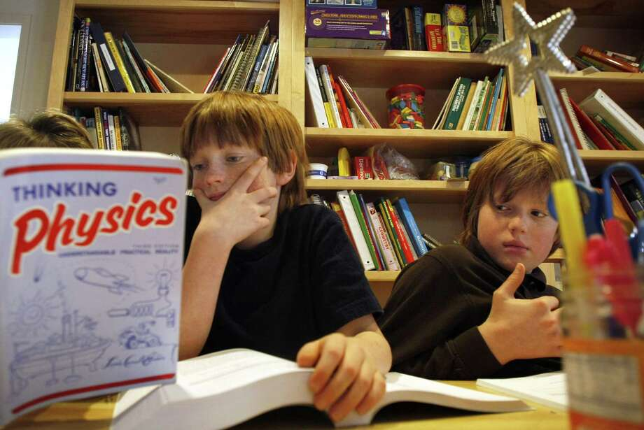 In a room filled with school resources, Will (left) and Max Schwarzer received home schooling from their mother, Debbie Schwarzer (concealed by the book) at their Los Altos, Calif., residence in 2008. Parents have the right to homeschool their kids if they deem it best method of instruction. Photo: Michael Macor /SFC / The Chronicle