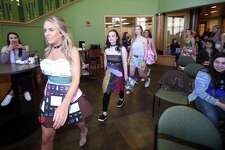 Quinnipiac University freshman Cara Sagnella (left) modeling a dress of recycled receipts and shopping bags and other students in the Eco-Fashion Design/Creativity for Wellness class participate in an eco-fashion show at the university's Carl Hansen Student Center in Hamden following the lecture, Fashion Systems and Micro-Utopias, by Timo Rissanen of the Parsons School of Design on April 20, 2018.