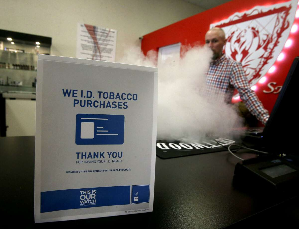 A sign on the counter at the Smoke to Live vape shop at 18154 Blanco in April reminds customers that tobacco products cannot be sold to people under the age of 18. As of Oct. 1, retailers, convenience stores, and smoke shop owners in San Antonio can no longer sell to anyone under 21 under a law passed by City Council. Three convenience store groups this week filed a federal lawsuit challenging the law. Showin vaping is store manager Jordan Studer.
