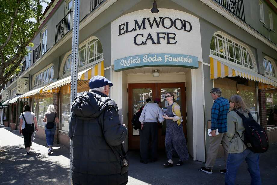 Visitors gather at the front door of the Elmwood Cafe on College Avenue to read the sign about the sudden closure of the Berkeley restaurant. Photo: Michael Macor / The Chronicle