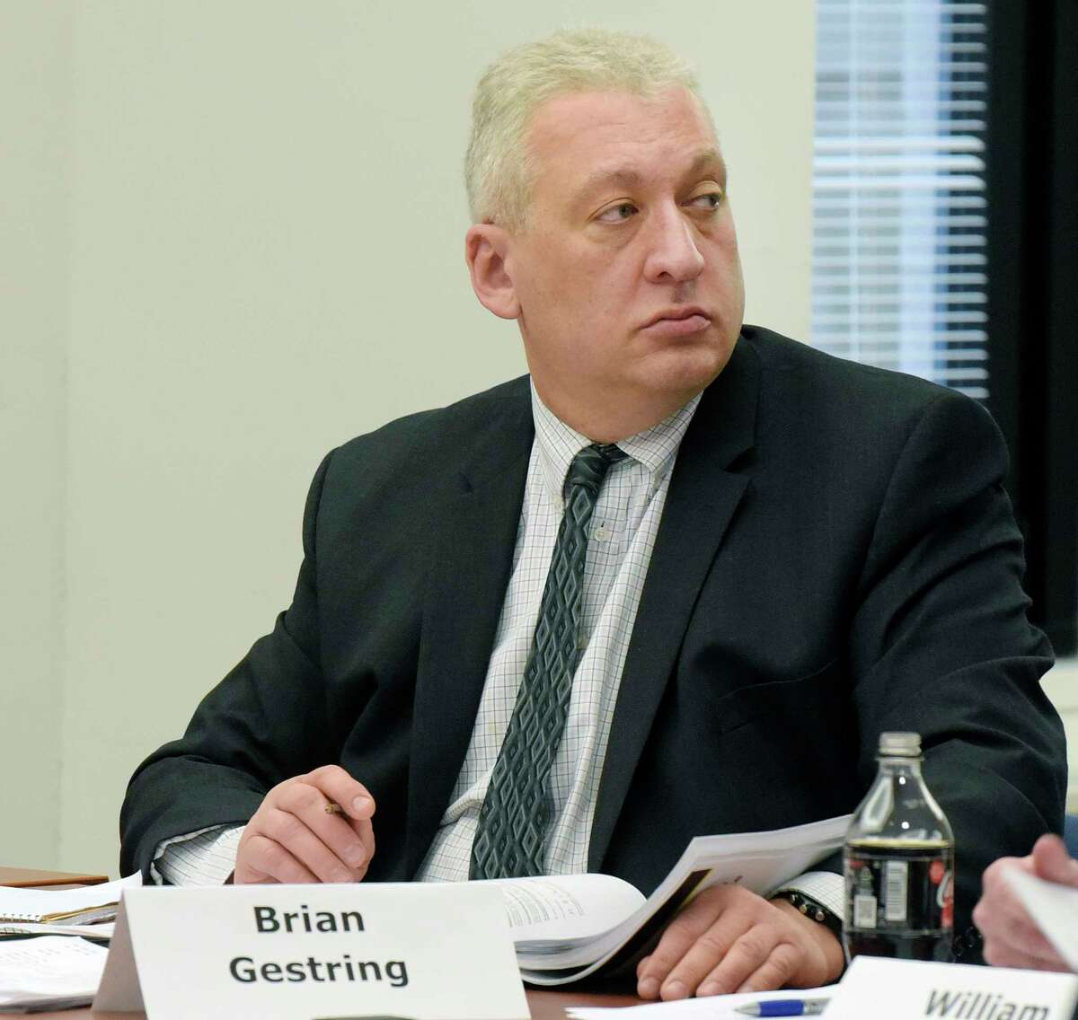 Brian Gestring, director of Forensic Science Office for the Department of Criminal Justice Services, takes part in a commission meeting on Wednesday, March 21, 2018, in Albany, N.Y. Gestring was fired Thursday, four days after the Times Union reported that he was never punished by the agency after an inspector general's investigation found that he had threatened female employees with physical violence and engaged in years of sexual harassment. (Paul Buckowski/The Albany Times Union via AP)
