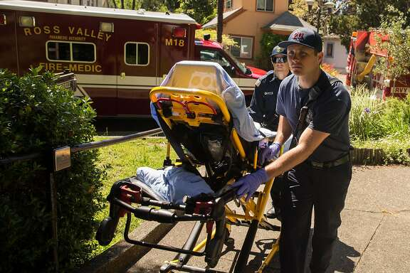 Marin County Fire EMS responders wheel a gurney into the Fairfax Police Station after receiveing a call Friday, April 20, 2018 Fairfax, Calif.