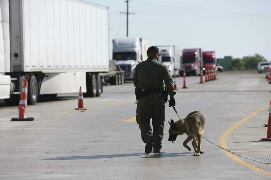 A U.S. Border Patrol K-9 unit works the tractor trailer lane at the Laredo checkpoint located about 29 miles north on IH-35 near Encinal, Texas, Thursday, April 12, 2018. Despite high-profile smuggling arrests using tractor-trailers and the media attention surrounding the deadly smuggling incident in San Antonio last year, Border Patrol continues to report a large amount of smuggling through tractor-trailers Photo: Photos By Jerry Lara / San Antonio Express-News / San Antonio Express-News