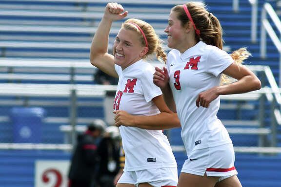 Houston Memorial senior defender Addie Gaetano, left, and sophomore defender Callie Hurley celebrate the Mustang's second goal against McAllen late in the second half of their UIL Class 6A State Semifinal Girls Soccer matchup at Birkelbach Field in Georgetown on April 20, 2018. (Photo by Jerry Baker/Freelance)