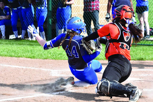Edwardsville catcher Taryn Brown, right, tags out Alton Marquette's Taylor Whithead at home plate to end the first inning on Friday.