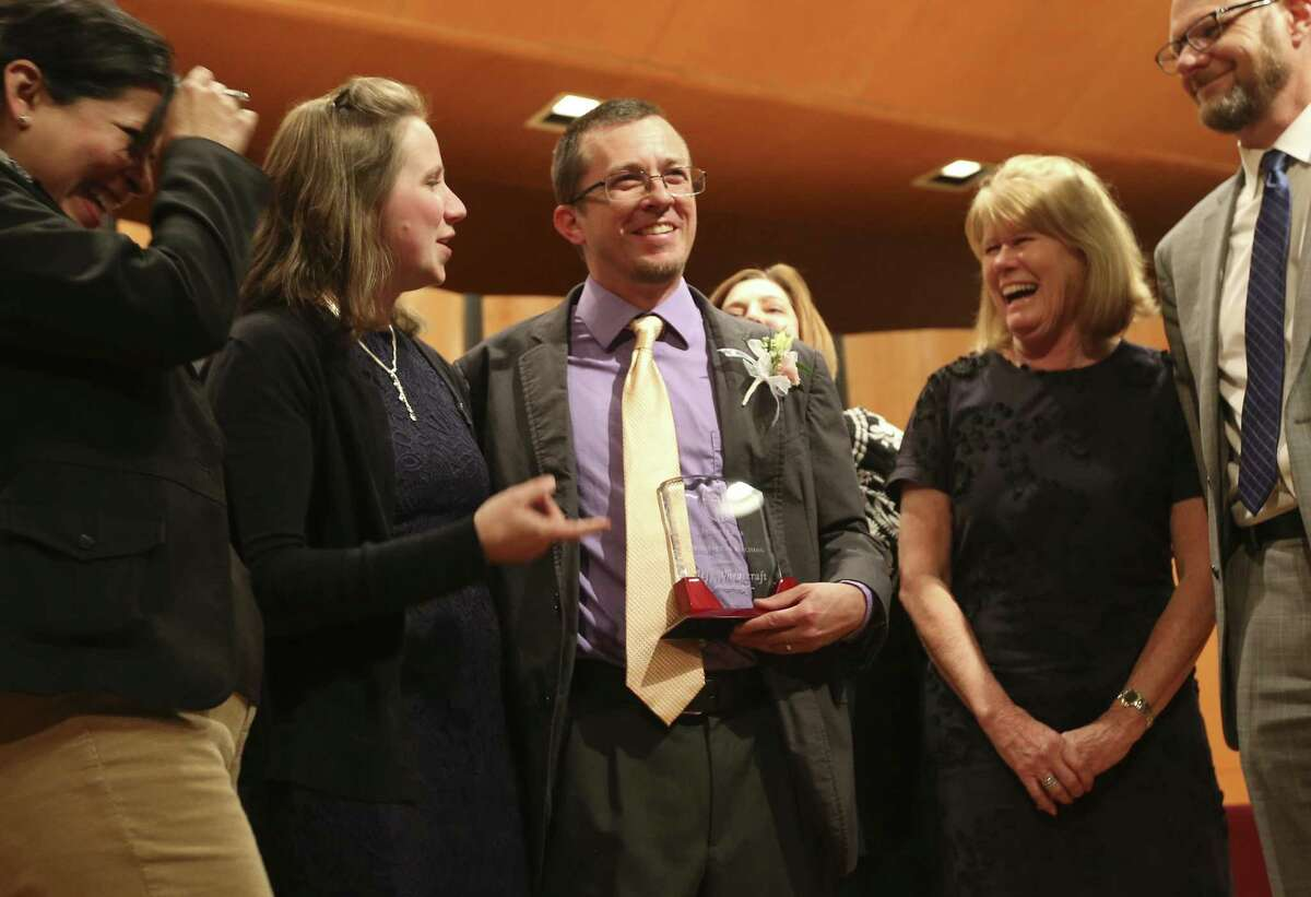 Alamo Height Junior High Science Teacher Jeff Wheatcraft (center) is congratulated by his wife Aimee (second from left) and AHISD Superintendent Kevin Brown (right) after he was award the Trinity Prize from a group of distinguished area educators who were honored at the annual Trinity Prize for Excellence in Teaching at Trinity University on Friday, Apr. 20, 2018. Wheatcraft along with Andrea Lucas of San Antonio Independent School District were awarded the Trinity Prize among the 19 educators this year. (Kin Man Hui/San Antonio Express-News)