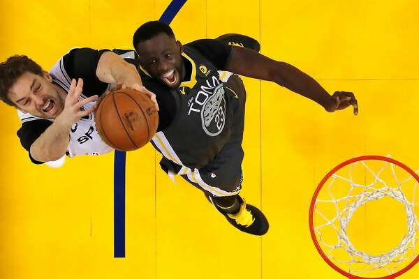 Draymond Green (23) and Pau Gasol (16) reach for a rebound in the second half as the Golden State Warriors played the San Antonio Spurs in Game 2 of the first round of the Western Conference Finals in Oakland, Calif., on Monday, April 16, 2018.