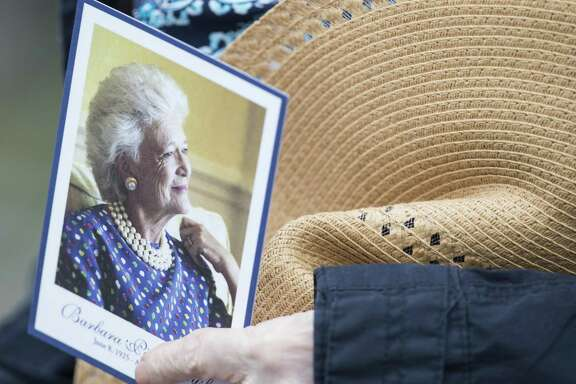 A photo of the late Barbara Bush is carried by a mourner after paying last respects to the former first lady on Friday, April 20, 2018, in Houston. ( Brett Coomer / Houston Chronicle )