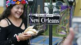 Elvira Rodriguez poses with her beignets Friday during a Taste of New Orleans at Sunken Garden Theater.