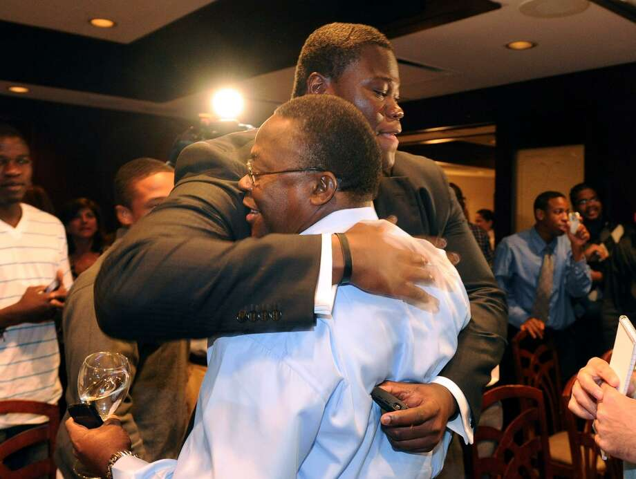 Vlad Ducasse hugs his father Delinois after being drafted by the New York Jets during the NFL draft pick gathering at Morton's Steakhouse in downtown Stamford on Friday April 23, 2010. Photo: Christian Abraham / File Photo / Connecticut Post