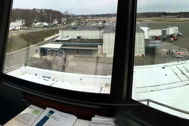 A panoramic composite photo of Tweed New Haven Airport through windows of the old tower, now the office of Timothy Larson, executive director of the Tweed airport authority, shows the main runway and the rows of houses right across Burr Street from the terminal.