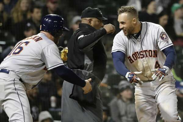 Houston Astros' George Springer, right, celebrates with Brian McCann after scoring on a throwing error by Chicago White Sox shortstop Tim Anderson during the fourth inning of a baseball game Friday, April 20, 2018, in Chicago. (AP Photo/Nam Y. Huh)