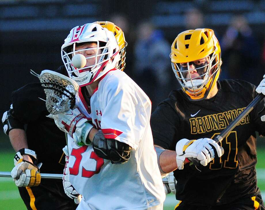 Leo Johnson (#33) of Greenwich loses the ball as he gets hit from behind by Wilson Stephenson (#11), right, of Brunswick, during the boys  high school lacrosse match between Brunswick School and Greenwich High School at Brunswick in Greenwich, Conn., Friday night, April 20, 2018. Photo: Bob Luckey Jr. / Hearst Connecticut Media / Greenwich Time