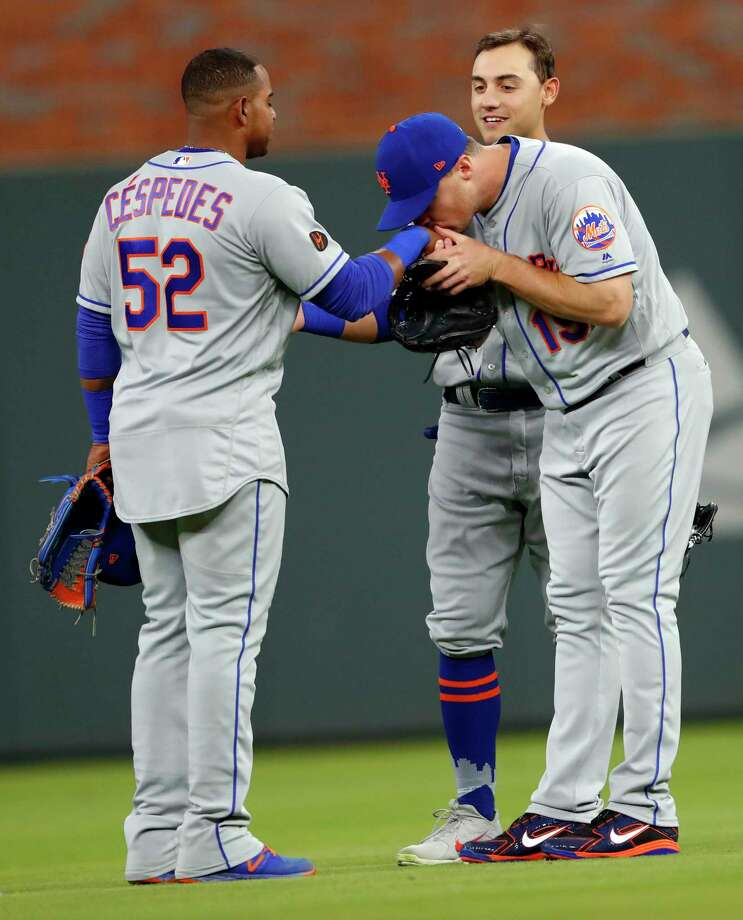 New York Mets' Jay Bruce (19) kisses Yoenis Cespedes (52) on on the hand as Michael Conforto (30) watches after the Mets defeated the Atlanta Braves 5-3 in 12 innings inning of a baseball game Friday, April 20, 2018, in Atlanta. Cespedes drove in the go-ahead run with a base hit in the 12th inning. (AP Photo/John Bazemore) Photo: John Bazemore / Copyright 2018 The Associated Press. All rights reserved.