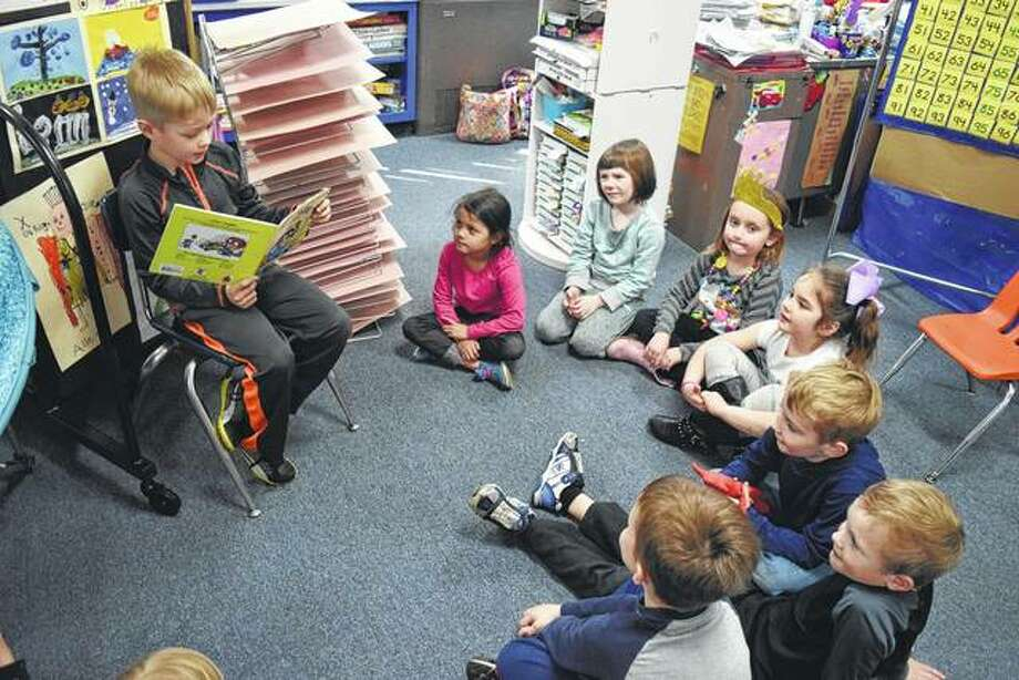 "Beckham Oldenettel (left), 6, of Jacksonville reads ""All By Myself"" by Mercer Mayer to teacher Jane Henderson's kindergarten class at Salem Lutheran School."