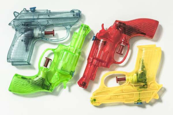 A group of colouful plastic water pistol are neatly arranged on a background