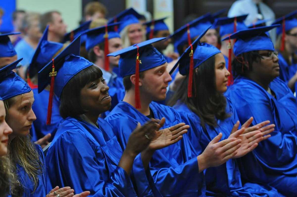 Nickia Dickerson, second from left, and Bethsy Crespo, second from right in the front row, applaud at the Washington Irving Educational Center in Schenectady during a GED graduation ceremony on June 9. ( Philip Kamrass / Times Union)