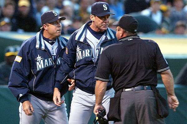 Seattle Mariners pitching coach Bryan Price, left, and manager Bob Melvin, center, argue Price's ejection from the game with crew chief Charlie Reliford, right, in the fourth inning against the Oakland Athletics Monday, July 26, 2004, in Oakland, Calif.  (AP Photo/Ben Margot)