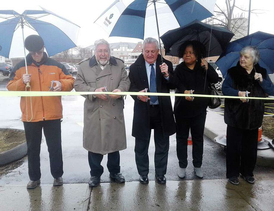 Norwalk Parking Authority Chairman Dick Brescia, left, Norwalk Public Library Board of Trustees Chairman Alex Knopp, Norwalk Mayor Harry Rilling, Library Assistant Director Sherelle Harris and Library Trustee Patsy Brescia cut a ribbon Thursday, April 19. 2018 for the newly-expanded parking lot next to the library. Photo: Robert Koch / Hearst Connecticut Media / Norwalk Hour