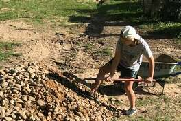 Ava Hale, a 15-year-old Senior Girl Scout in Troop 11864, shovels rocks into place along the drainage pathway at her school as part of her flood mitigation Gold Award Project.