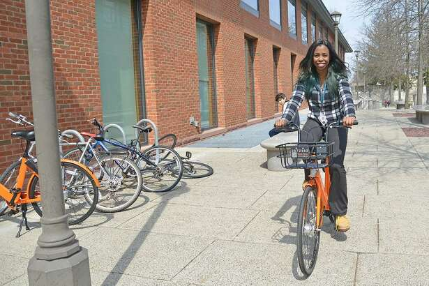 Erica Wright, project assistant for Physical Plant Facilities, tests a Spin bike as part of Wesleyan University's new bikeshare program.