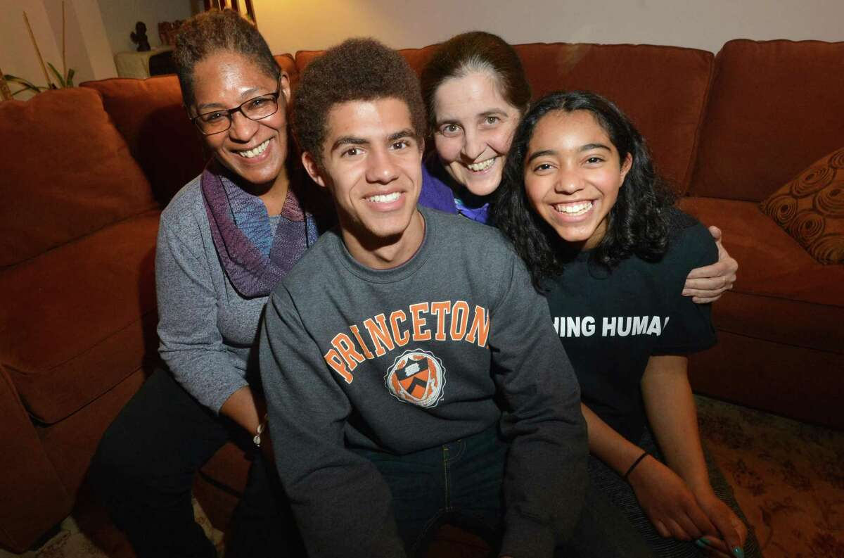 Chaz Bethel-Brescia sits with his family, his mothers Phyllis Bethel and Tina Brescia and sister Nia on Tuesday April 17, 2018 in Norwalk Conn. Chaz was accepted to four ivy league shools and MIT, his senior essay was about his experience being raised by two mothers.