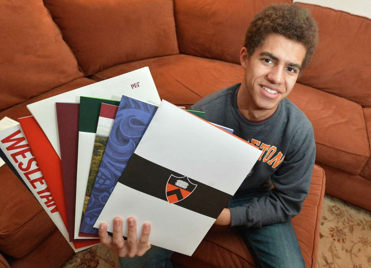 Chaz Bethel-Brescia fans out the college folders with letters of acceptance on Tuesday April 17, 2018 in Norwalk Conn. Chaz was accepted to four ivy league schools and MIT, his senior essay was about his experience being raised by two mothers.
